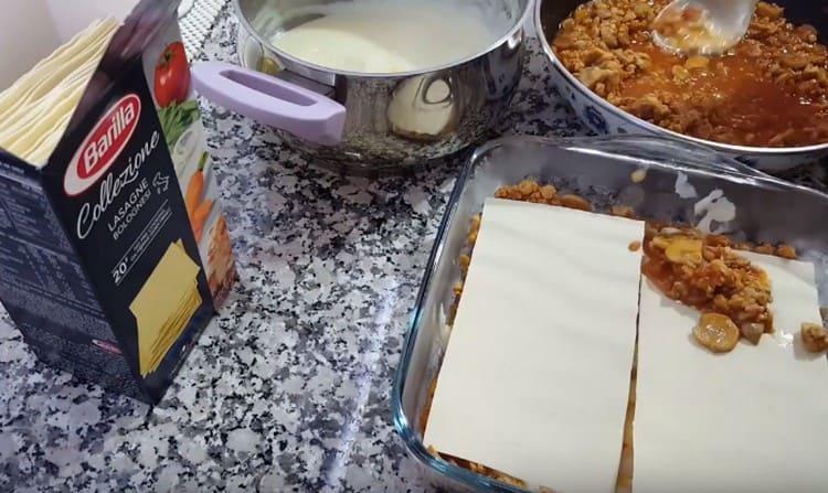 Чередуем листы лазаньи и соусы, собирая блюдо.