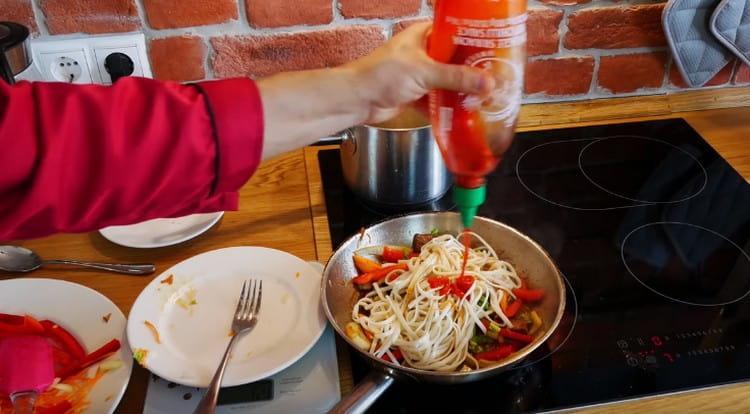 Выкладываем на сковороду лапшу, добавляем соевый соус и соус шрирача.