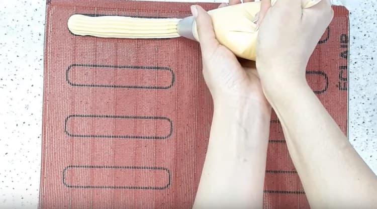 Отсаживаем эклеры на силиконовый коврик.