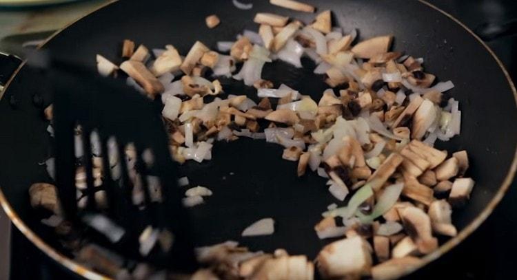 К луку добавляем чеснок и грибы, жарим вместе.