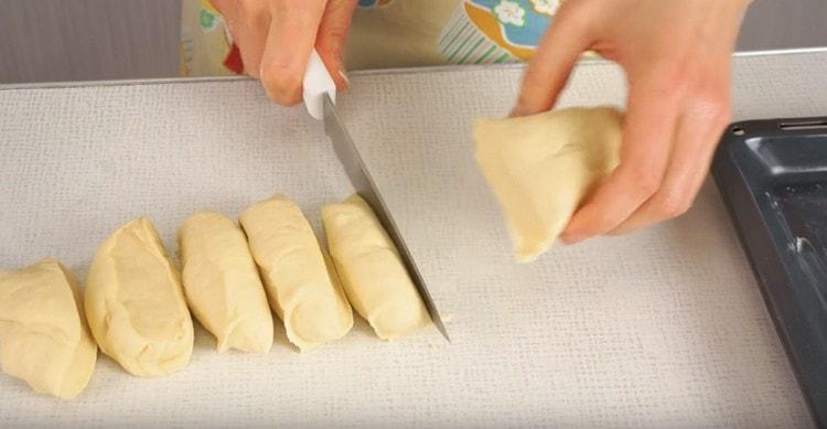 Тесто делим на две части, каждую из них скатываем валиком и делим на порции.