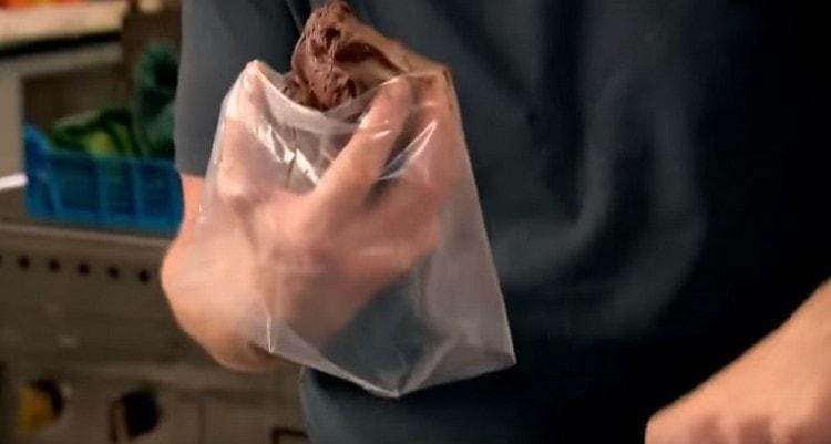 На руку надеваем кондитерский мешок с насадкой, выкладываем в него шоколадную начинку.