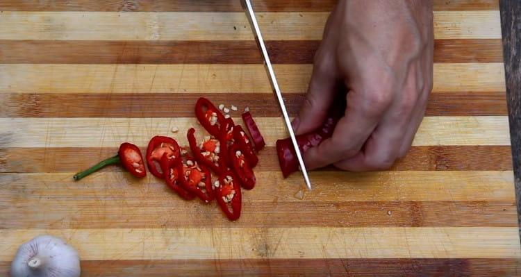 Мелко нарезаем перец чили.