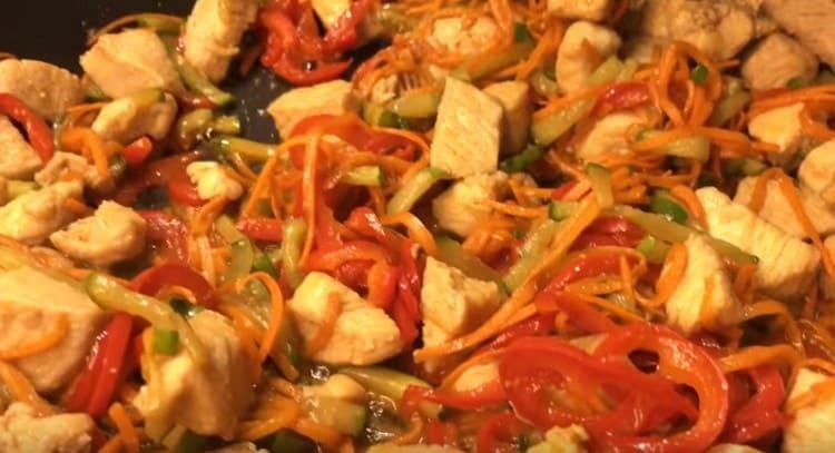 К курице на сковороду добавляем все овощи, перемешиваем.