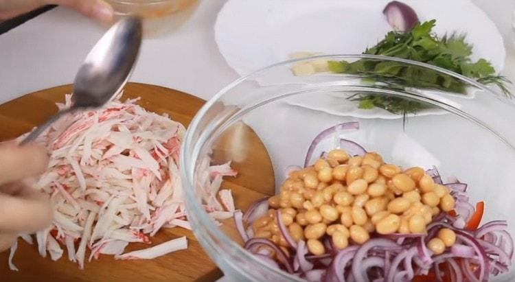 В миску с уже подготовленными компонентами выкладываем консервированную фасоль.