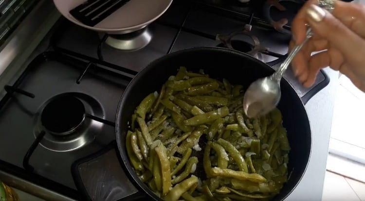 Фасоль добавляем на сковороду к луку, солим и перчим блюдо.