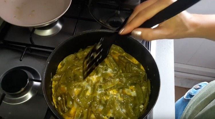 Выливаем на сковороду к фасоли яйца, перемешиваем.