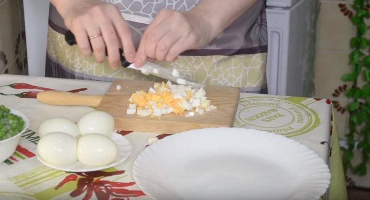 Нарезаем кубиком отварные куриные яйца.