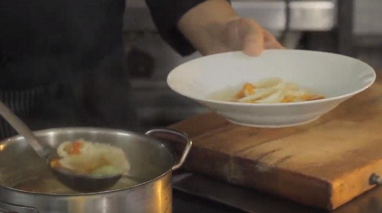 Раскладываем суп из кальмаров по тарелкам.