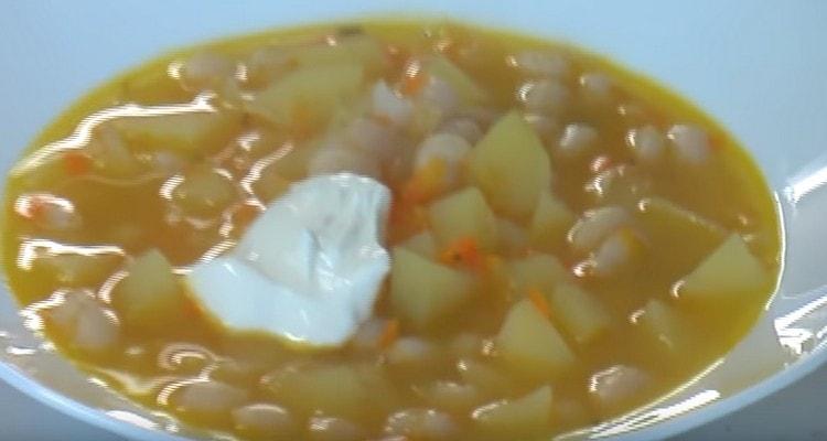 Подать суп с фасолью можно со сметаной.