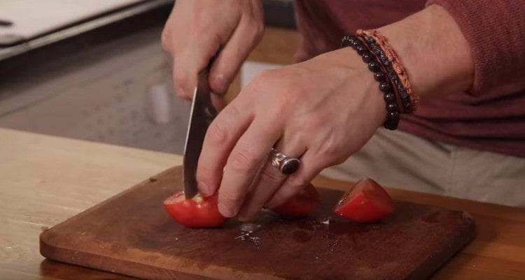 Добавляем в кастрюлю также разрезанный на 4 части помидор.
