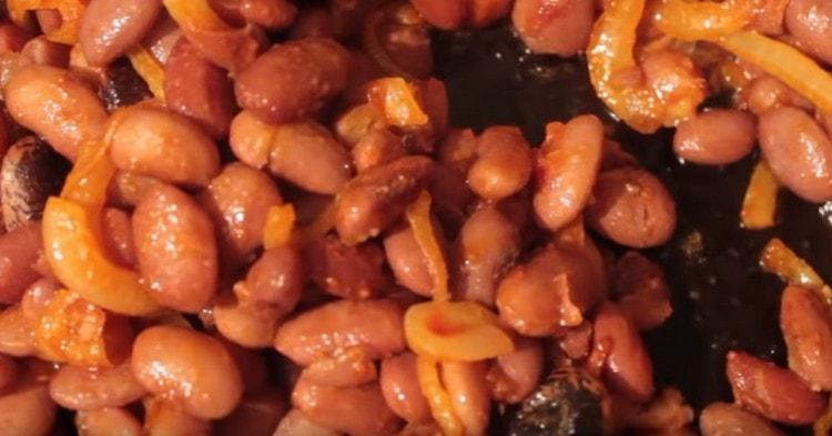К луку с томатной пастой перекладываем отваренную до готовности фасоль.