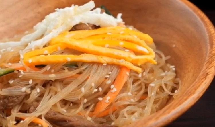 При подаче фунчозу с говядиной украшает кунжутом и обжаренными ломиками яичного белка и желтка.