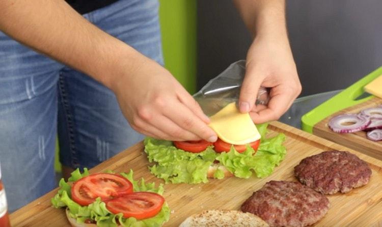 На помидоры выкладываем ломтик сыра.