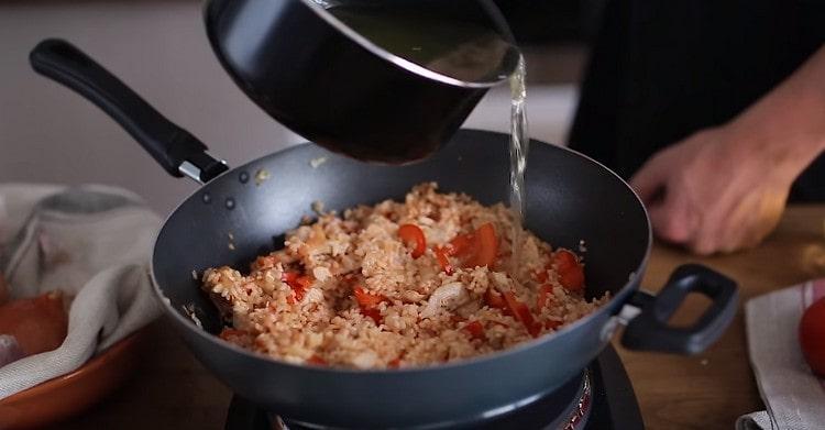 Бульон с шафраном добавляем на сковороду с будущей паэльей.