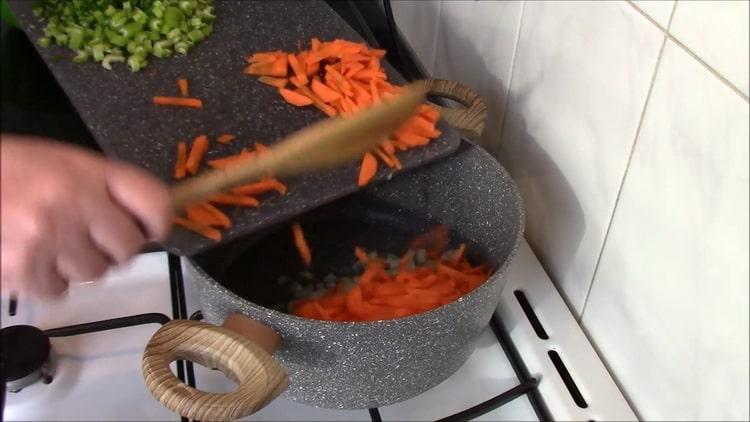 Для приготовления перловки с тушенкой обжарьте овощи