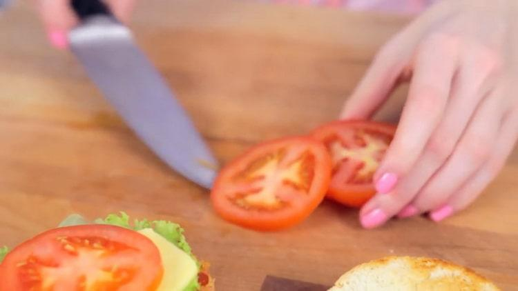 Для приготовления крабсбургера, нарежьте помидор