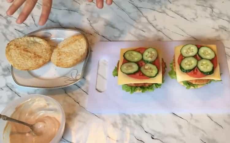 Для приготовления чикенбургера, положите овощи на булку