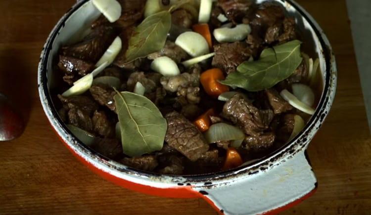 Обжаренное мясо добавляем к овощам, добавляем чеснок, лавровый лист, специи.