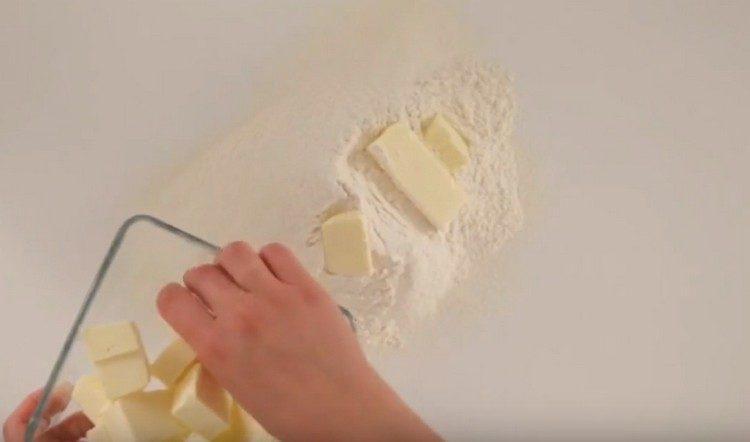 В посеянную муку выкладываем нарезанное кусочками масло.