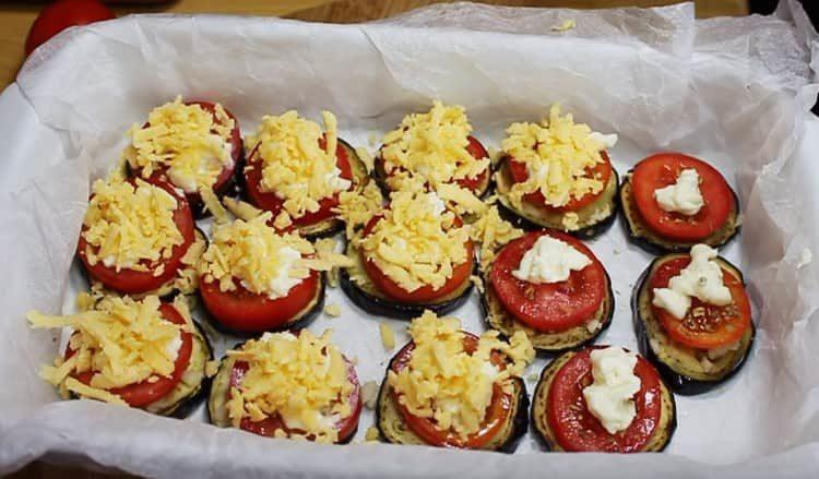 Поверх помидоров выкладываем сливочный сыр, посыпаем его тертым сыром.