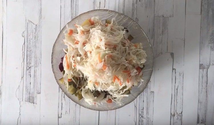Последней добавляем в салат квашеную капусту.