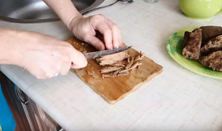 Тонкой соломкой нарезаем остывшую печень.
