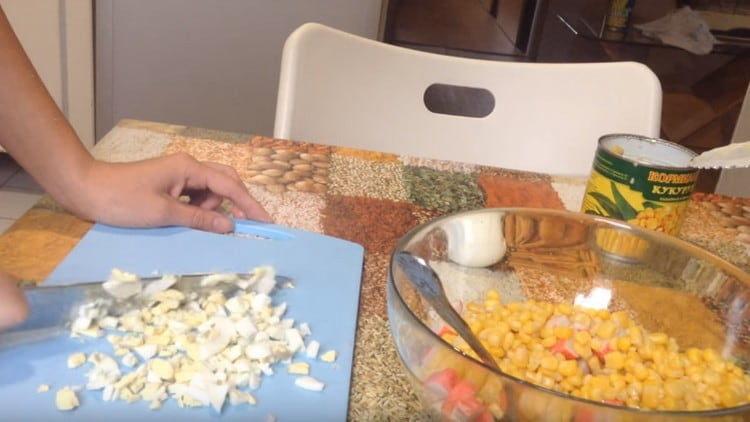 Нарезаем отварные яйца и добавляем в салат.