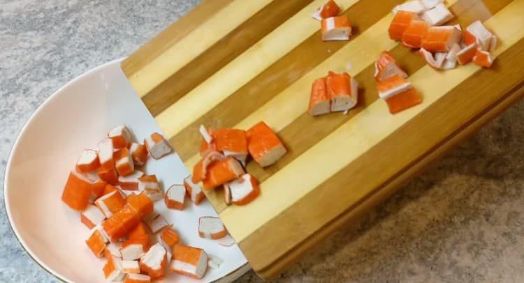 Нарезаем крабовые палочки и выкладываем в салатник.