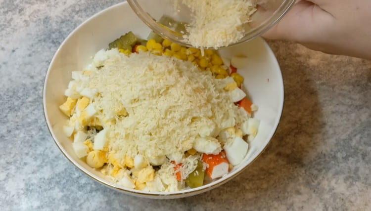 Добавляем в салат натертый на мелкой терке сыр.