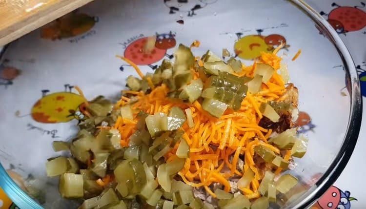 Добавляем соленые огурцы в салат.