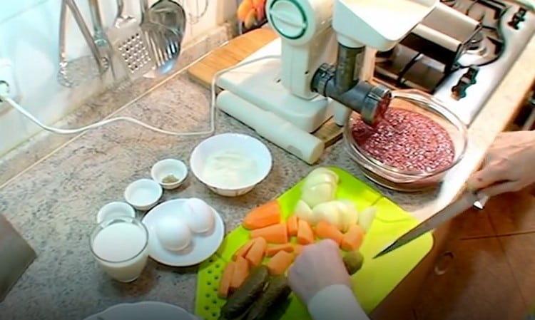Вместе с печенью пропускаем через мясорубку лук, морковь, соленые огурцы.