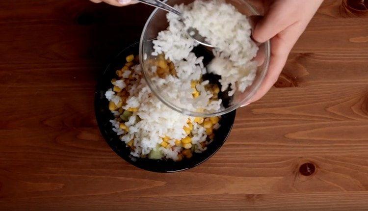 Добавляем к огурцу и крабовым палочкам отварной рис и кукурузу.