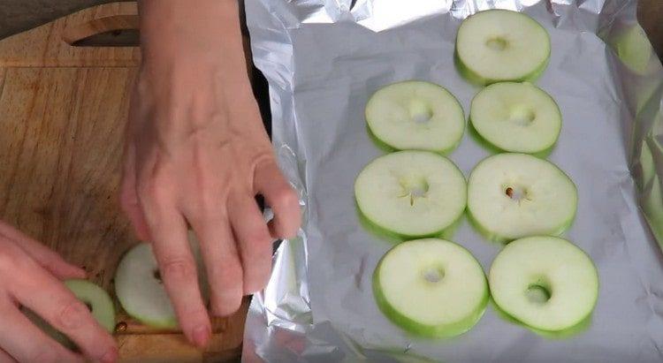 Нарезаем яблоки тонкими кружочками и выкладываем на застеленный фольгой противень.