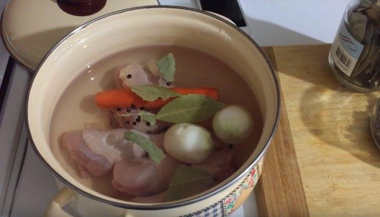 В кастрюлю выкладываем куриные ножки, овощи, перец, лавровый лист.