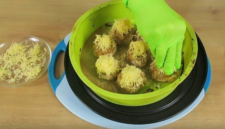 Присыпаем фаршированные шампиньоны сыром и ставим в духовку, чтобы образовалась румяная корочка.