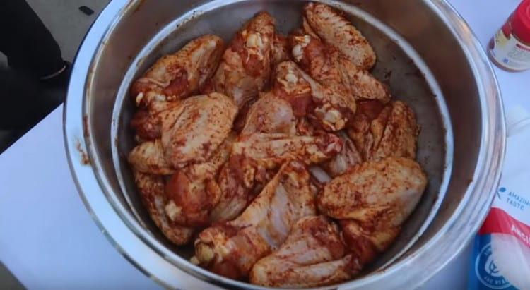 Перемешиваем крылышки с маслом и специями.