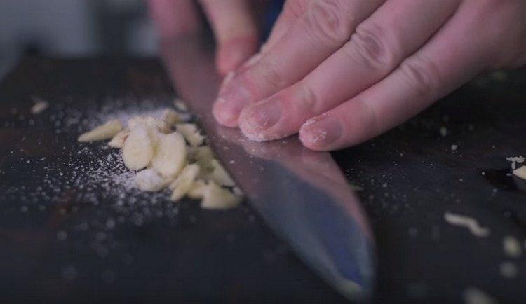 Перетираем чеснок с солью.