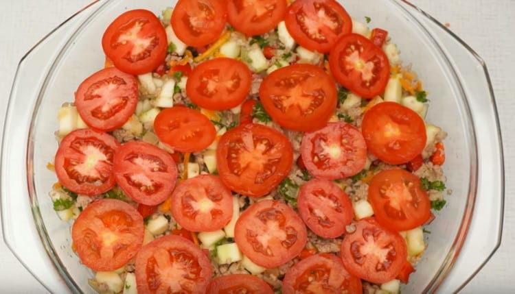 Поверх заготовки раскладываем нарезанные кружочками помидоры.