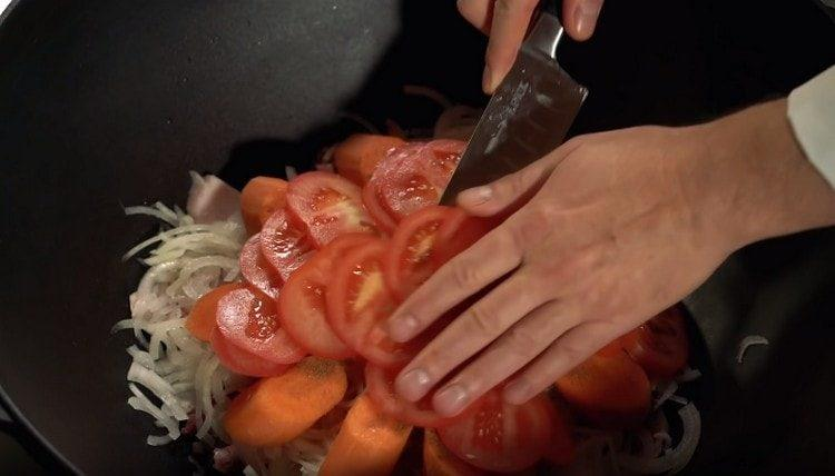 Поверх моркови выкладываем нарезанный кружочками помидор.