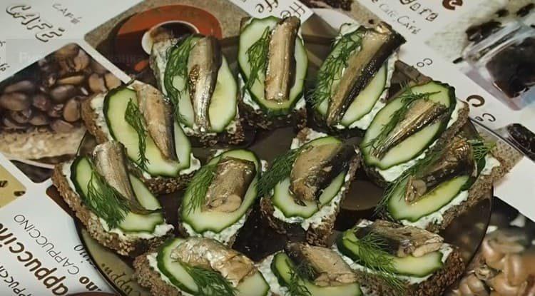 Украшаем бутерброды со шпротами и свежим огурцом веточкой укропа.