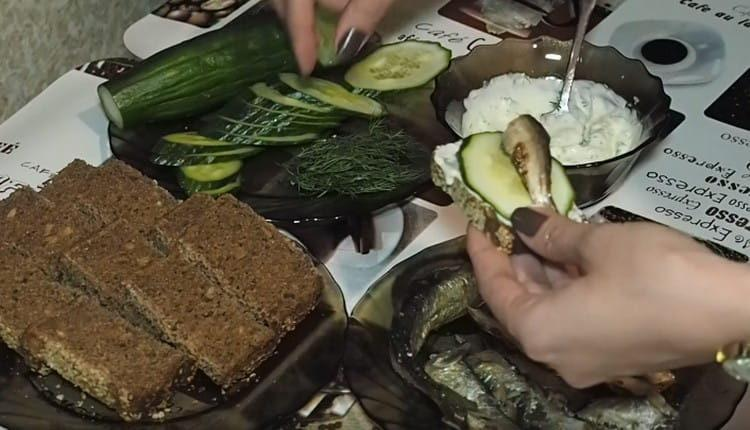 Ломтик хлеба намазываем соусом, выкладываем кружочек огурца и шпрот.