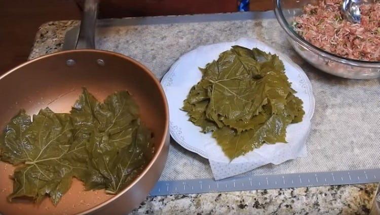 Дно кастрюли для готовки долмы застилаем виноградными листьями.