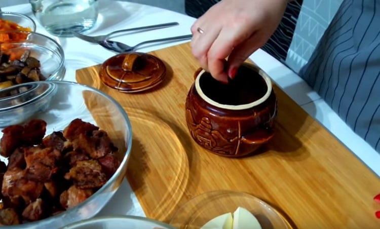 На дно горшочка для запекания выкладываем перец горошком и лавровый листик.