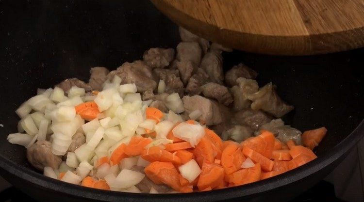 Добавляем к мясу лук и морковь.
