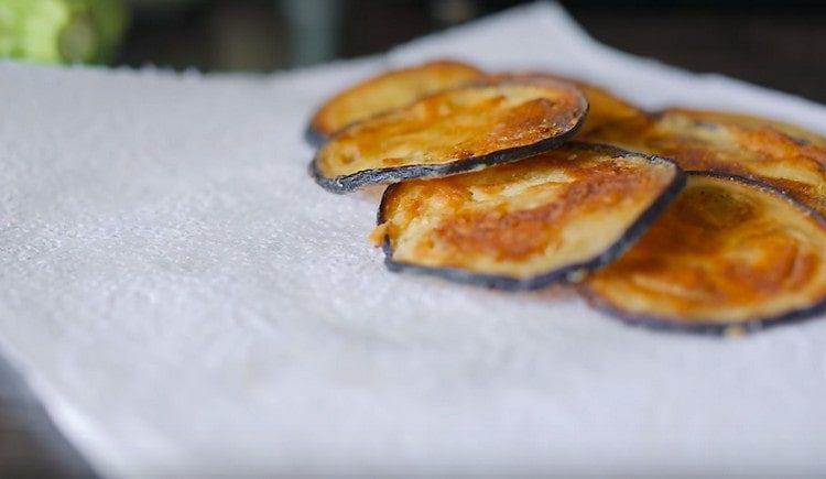 Перекладываем чипсы из баклажанов на салфетки.