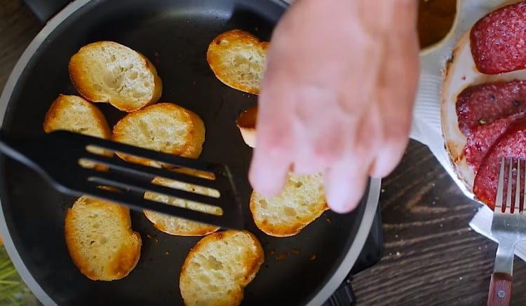 На сковороде обжариваем ломтики французского багета.