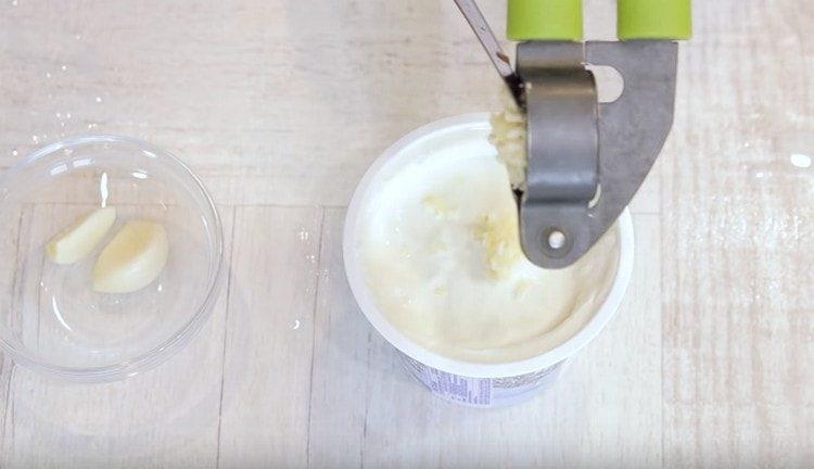 В сметану выдавливаем чеснок и перемешиваем.