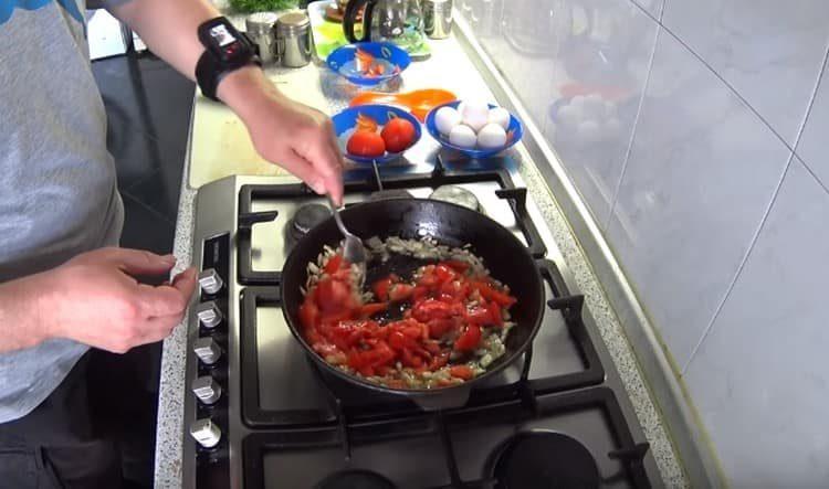 Добавляем к луку нарезанные кусочками помидоры.