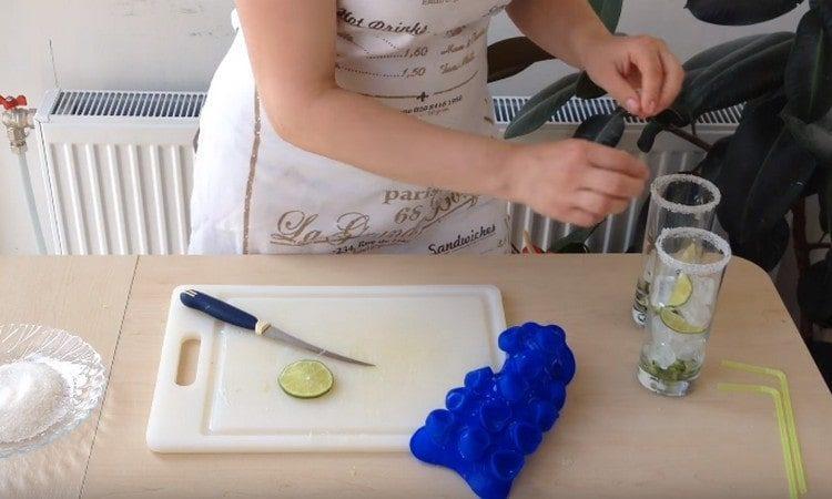В стаканы выкладываем лед и нарезанный лайм